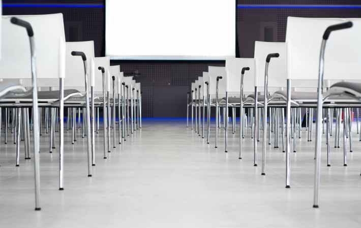 Chairs lined up for a presentation in front of a screen.