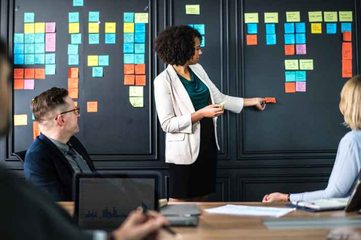 A woman placing a post-it on a board for an affinity diagram while others watch.