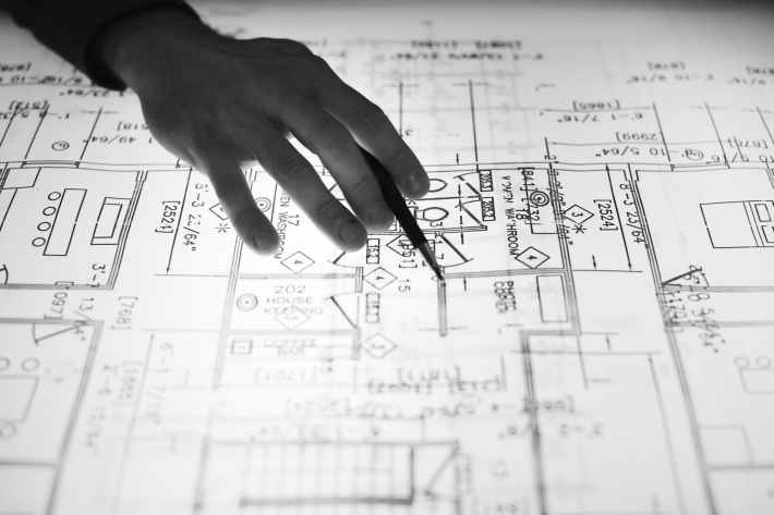 A hand pointing out something on a blueprint.